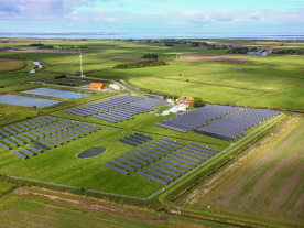 The aerial photograph shows the hybrid power plant with energy storage system on the North Sea island of Pellworm. The system at top right is being fitted with a new aluminium substructure; the one in the upper left of the photo was built on an almost maintenance-free substructure made of tropical wood. (Photo: HanseWerk AG)